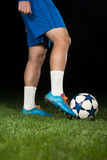 Legs Of Player With Ball On Dark Background Royalty Free Stock Photos