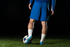 Legs Of Player With Ball On Dark Background Stock Images