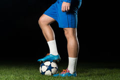 Legs Of Player With Ball On Dark Background Stock Photo