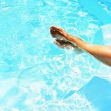 Legs in the pool with clean water in hot sunny day. Summer background for traveling and vacation. Holiday idyllic. Stock Images