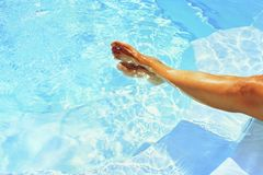 Legs in the pool with clean water in hot sunny day. Summer background for traveling and vacation. Holiday idyllic. Stock Photo