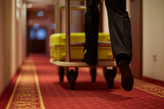 Legs of porter. Porter moving luggage in cart down aisle covered by red carpet stock images