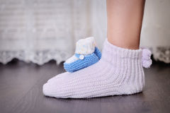 Legs of pregnant mother and little knit baby shoes Royalty Free Stock Photos