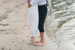Legs pretty strong young loving couple on the beach over the river. Next to a bouquet, lifestyle, concept, love, tenderness Stock Images