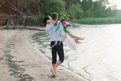 Legs pretty strong young loving couple on the beach over the river Royalty Free Stock Photography
