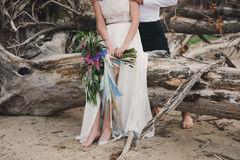 Legs pretty strong young loving couple on the beach over the river. Next to a bouquet, lifestyle, concept, love, tenderness Royalty Free Stock Photography