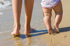 Legs of a pretty woman walking in water  with her daugther. Nice legs of a pretty woman walking in water  with her baby Royalty Free Stock Photography