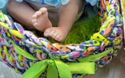 Legs of a realistic baby doll in a multi-colored basket stock images