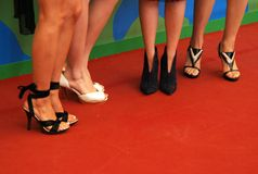 Legs on red carpet. Several woman shoes on red carpet Stock Image