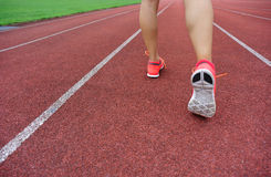 Legs on red running track in stadium Stock Photography