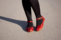 Legs and red shoes on pavement Royalty Free Stock Photo