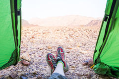 Legs in red sneakers near green tent. Happy traveller relax during trip in Israel desert Royalty Free Stock Images