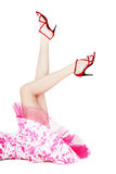 Legs in red stilettos. Legs of woman in red stilettos and pink dress lying on white background Royalty Free Stock Image