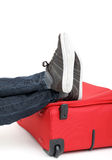 Legs on red suitcase Stock Photography