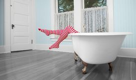 Striped legs over bath tub in vintage bathroom royalty free stock images