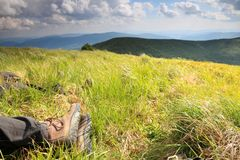 Legs of resting tourist in the mountain landscape. Royalty Free Stock Photos