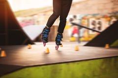 Legs on rollerblades. Orange slalom cones. Training in skatepark Stock Photos