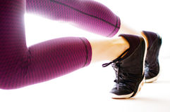 Legs in running position with black shoes. Legs in running position shoes with black shoes and yoga pants on white background Stock Photo