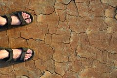 Legs with sandals on dry cracked earth. Royalty Free Stock Photos