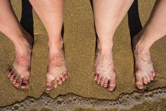 Legs on a sandy beach in Palma de Mallorca, Spain. The photo is taken in summer on a bright and sunny day Royalty Free Stock Photos