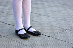 Legs schoolgirl in black shoes and white tights stock photography