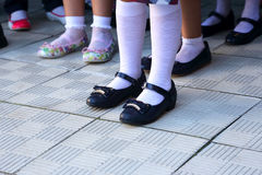 Legs of schoolgirls in different shoes on the sidewalk Royalty Free Stock Photography