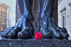 Legs of a sculpture of the Atlas of the Hermitage. With a red carnation Royalty Free Stock Images