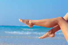 Legs on sea background. Woman legs on blue sea background stock photography