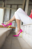 Legs and sexy pink high heels sitting relaxed. Concept close up image of woman sitting in Elegant sexy pink high heel stiletto shoes, sitting relaxed on bench Stock Photography