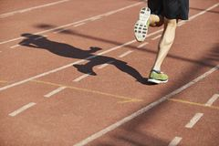 Male athlete running on track. Legs and shadow of a male athlete running on track Royalty Free Stock Image