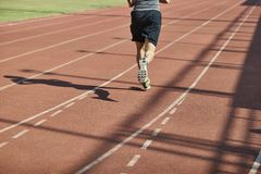 Male athlete running on track. Legs and shadow of a male athlete running on track Royalty Free Stock Photography