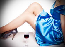 Legs in shoes  and a glass of red wi Stock Photography