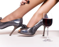 Legs in shoes and a glass of red wi Stock Photos