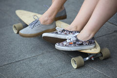 Legs in shoes with long boards Stock Image