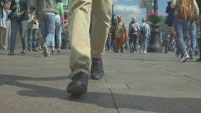Legs And Shoes Moving On Sidewalk. Feet of young male pedestrians walking on the city street on summer day stock footage