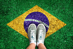 Legs and shoes standing on a floor colored with brazilian flag Royalty Free Stock Photo