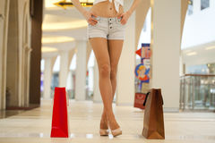 Legs of shopaholic wearing jeans shorts while carrying several p. Close up Legs of shopaholic wearing jeans shorts while carrying several paperbags Royalty Free Stock Photos