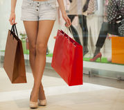 Legs of shopaholic wearing jeans shorts while carrying several p. Close up Legs of shopaholic wearing jeans shorts while carrying several paperbags Royalty Free Stock Photo