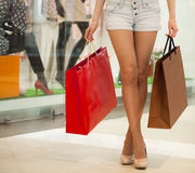 Legs of shopaholic wearing jeans shorts while carrying several p Royalty Free Stock Photo