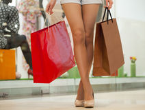 Legs of shopaholic wearing jeans shorts while carrying several p. Close up Legs of shopaholic wearing jeans shorts while carrying several paperbags Stock Photo