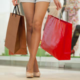 Legs of shopaholic wearing jeans shorts while carrying several p. Close up Legs of shopaholic wearing jeans shorts while carrying several paperbags Stock Image