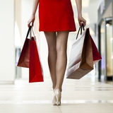 Legs of shopaholic wearing red dress while carrying several pape Stock Photography