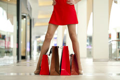 Legs of shopaholic wearing red dress while carrying several pape Stock Photo