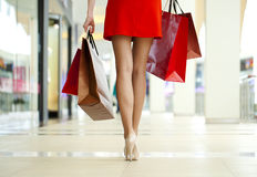 Legs of shopaholic wearing red dress while carrying several pape Royalty Free Stock Photo