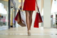 Legs of shopaholic wearing red dress while carrying several pape Royalty Free Stock Photos