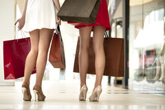 Legs of shopaholic wearing red dress while carrying several pape Royalty Free Stock Image