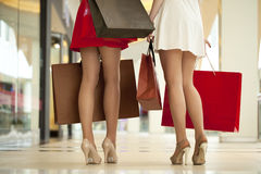 Legs of shopaholic wearing red dress while carrying several pape Stock Photos