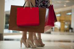 Legs of shopaholic wearing red dress while carrying several pape Royalty Free Stock Images