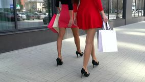 Legs of shopaholics with shopping bags walking down mall. beautiful female legs. shoping legs. close-up of female legs stock footage
