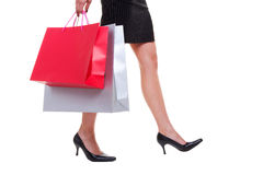 Legs and shopping bags. Females legs and colourful shopping bags isolated on white background Royalty Free Stock Photography